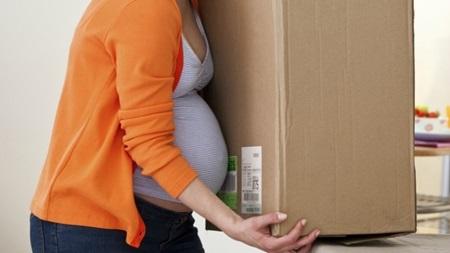 重い荷物を持つ妊婦